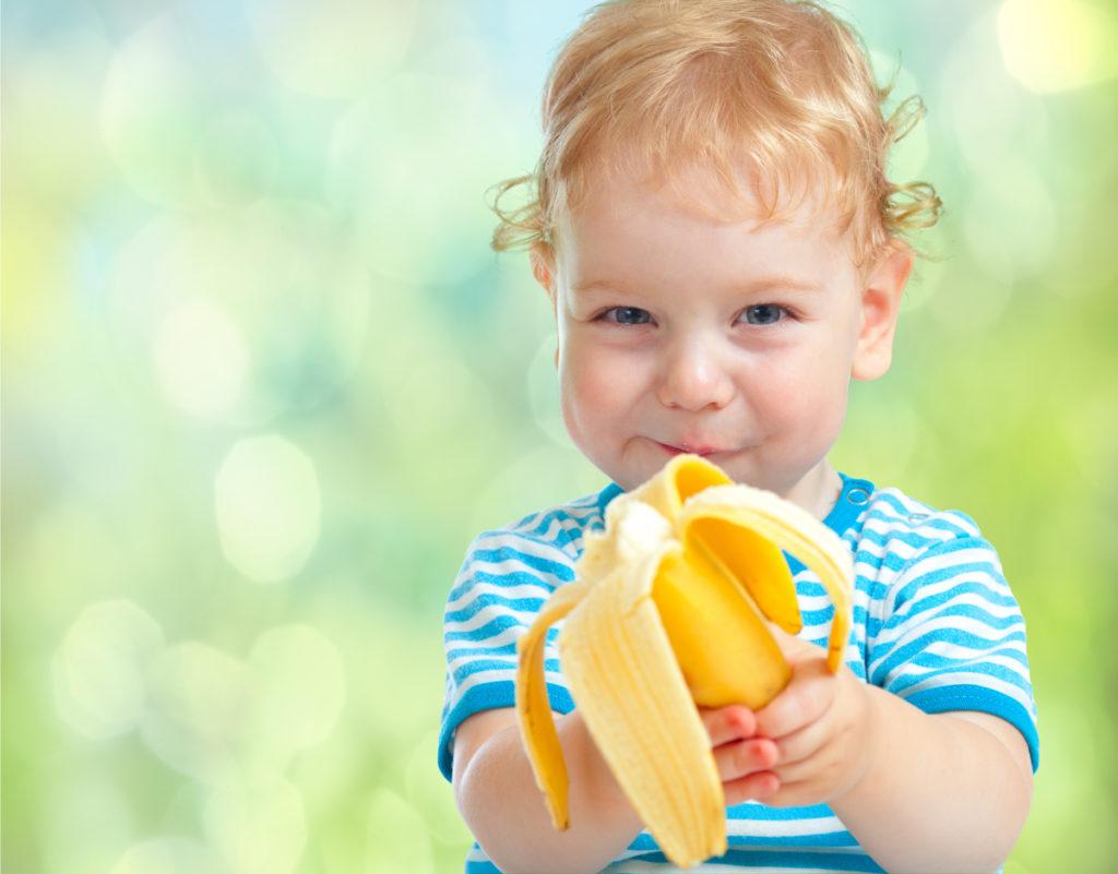 ребенок держит банан