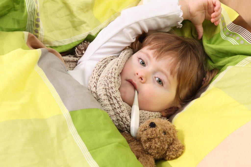 ребенок лежит в постели с градусником во рту