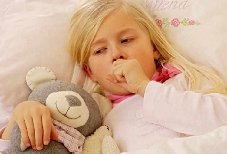 девочка кашляет, лежа в кровати