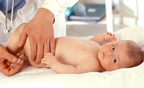 малышу делают прививку в бедро