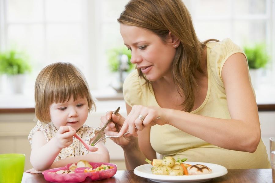 мама накладывает девочке в тарелку еду