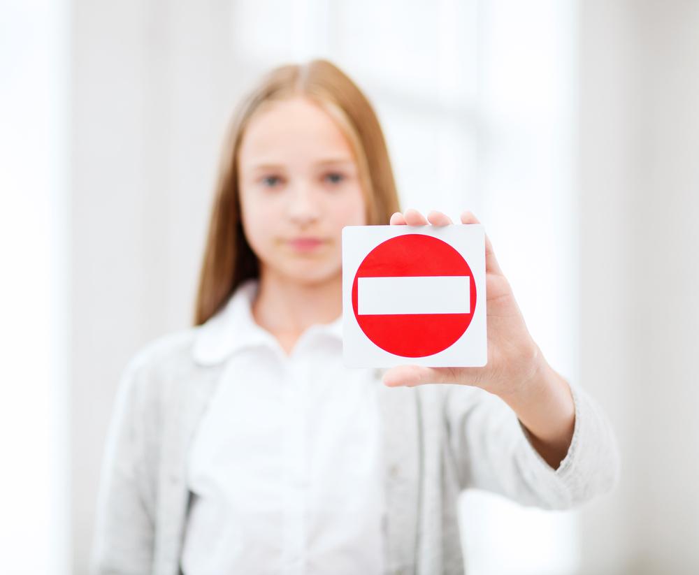 девочка держит в руках знак