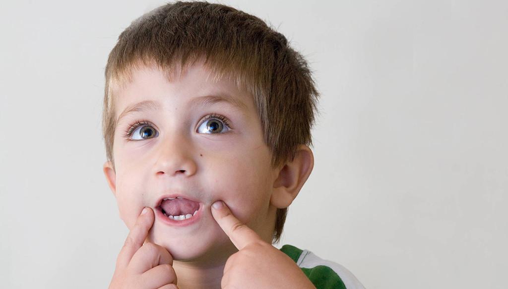 мальчик держит пальцы возле рта