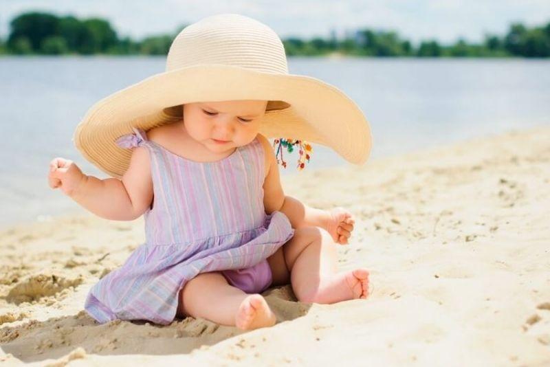 девочка в головном уборе сидит на берегу