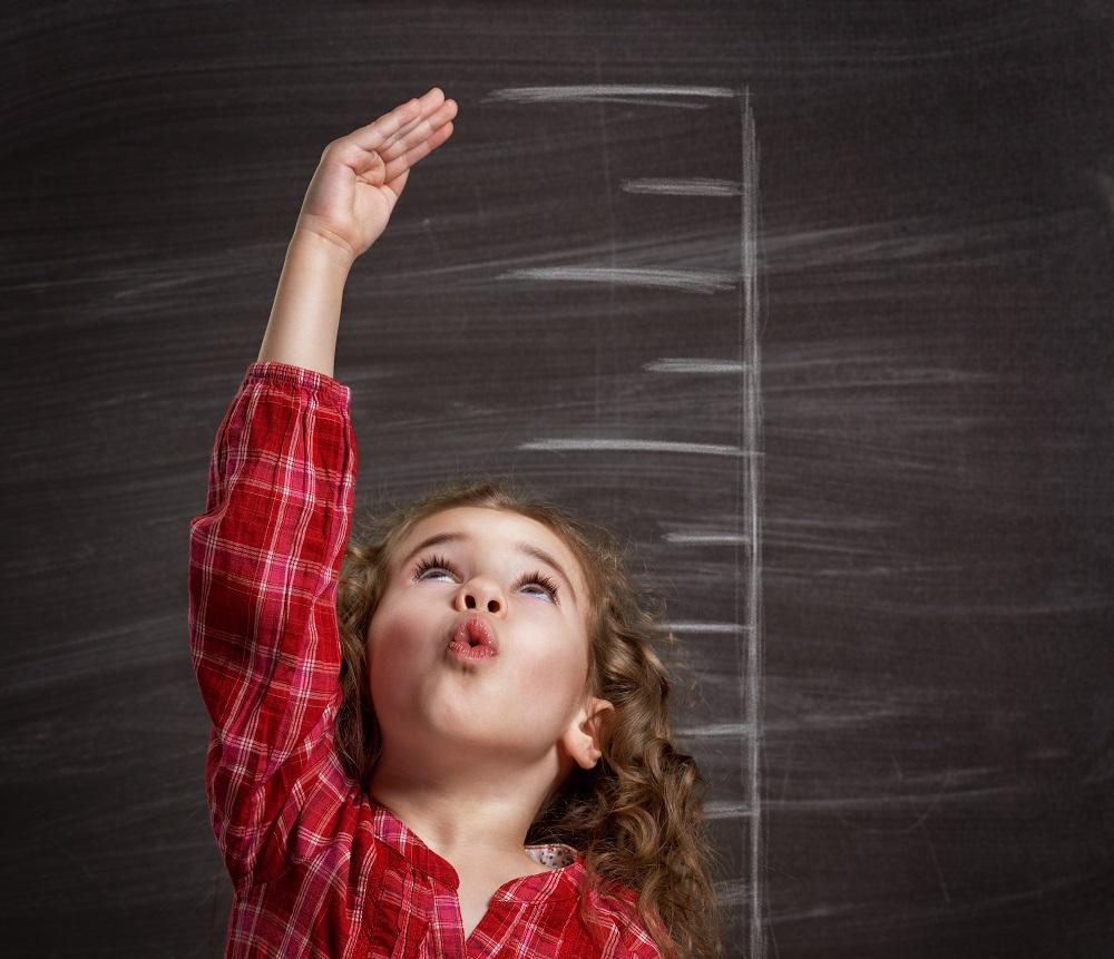 девочка тянется рукой к последнему делению мерной шкалы роста