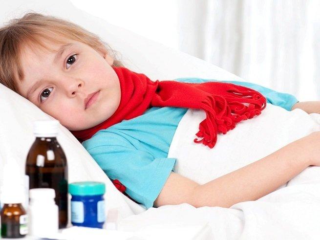 больной ребенок в красном шарфе лежит под одеялом, а рядом с ним стоят лекарства