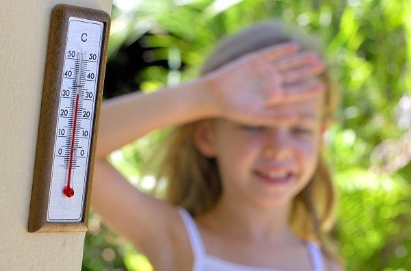 девочка прикрывает лоб от жары - на градуснике 33 в тени