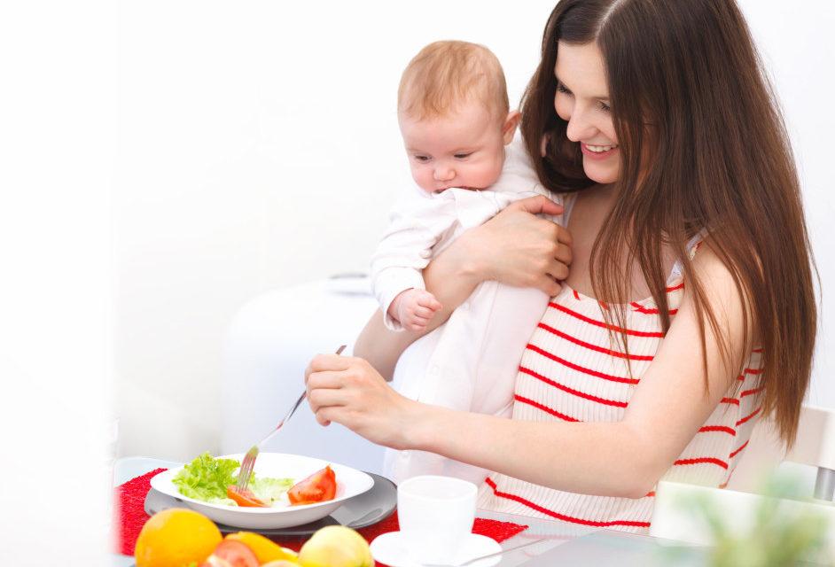 девушка накалывает помидор вилкой держа ребенка на руках