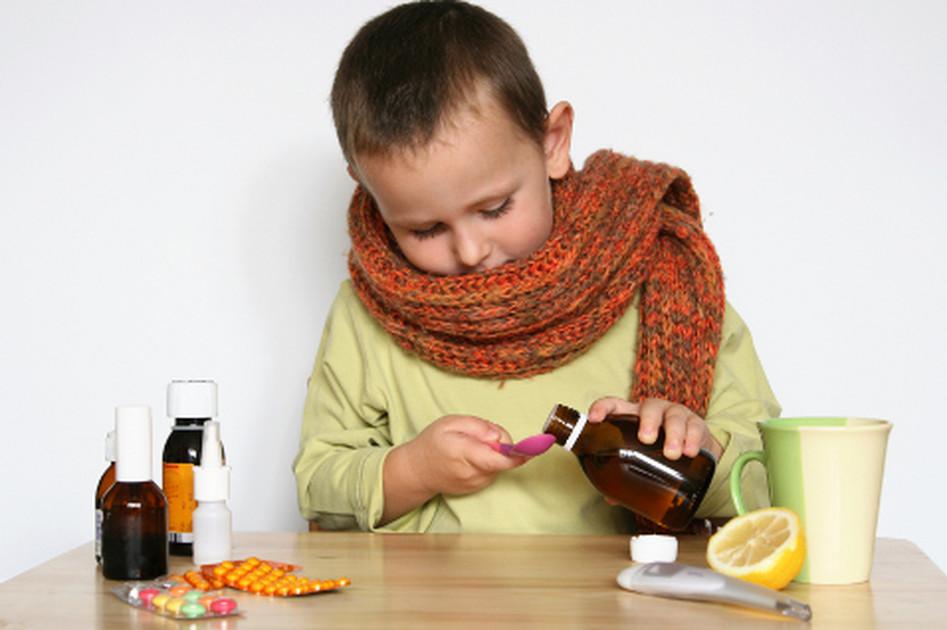 ребенок в шарфе за столом окруженный лекарствами наливает сироп в ложечку