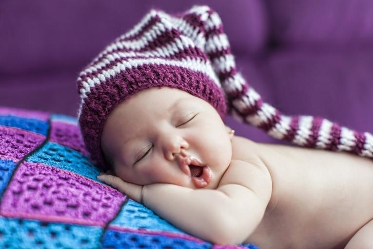 голый ребенок в шапке спит открыв рот