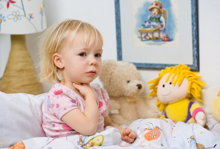 девочка держится за горло (сидя под одеялом на кровати с двумя мягкими игрушками)