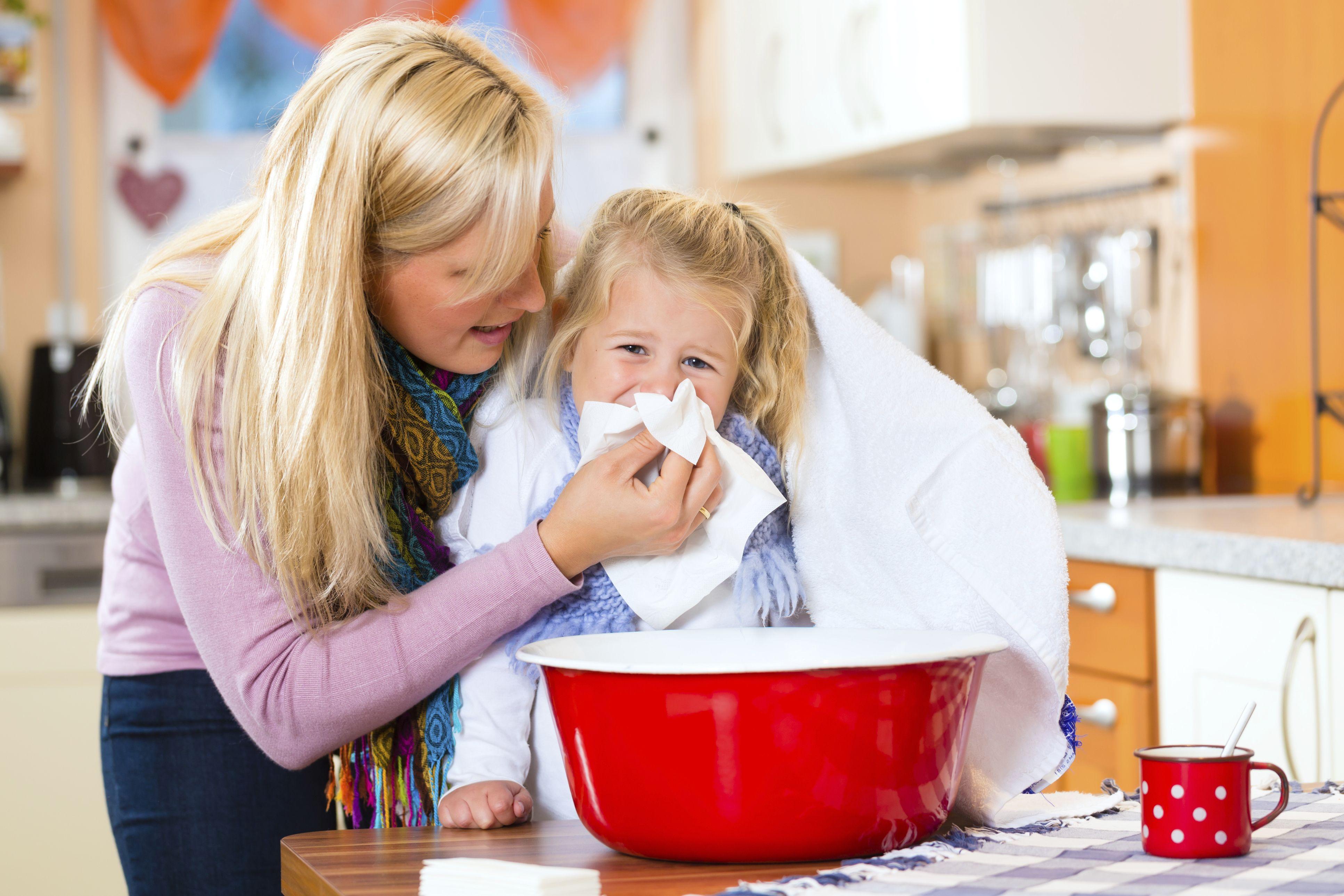 мама вытирает девочке нос салфеткой после того, как та, предположительно, дышала паром под полотенцем над красной миской