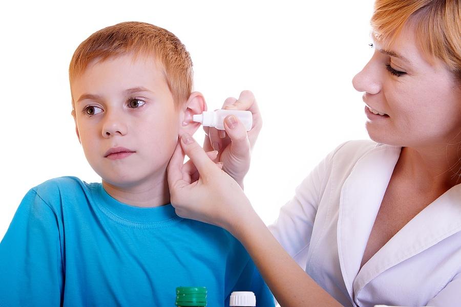 девушка врач закапывает мальчику в ухо