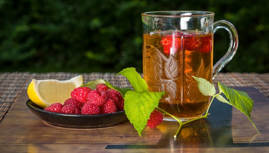 чашка чая с малиной и онаже на тарелке с лимоном на столе + три листика зеленых