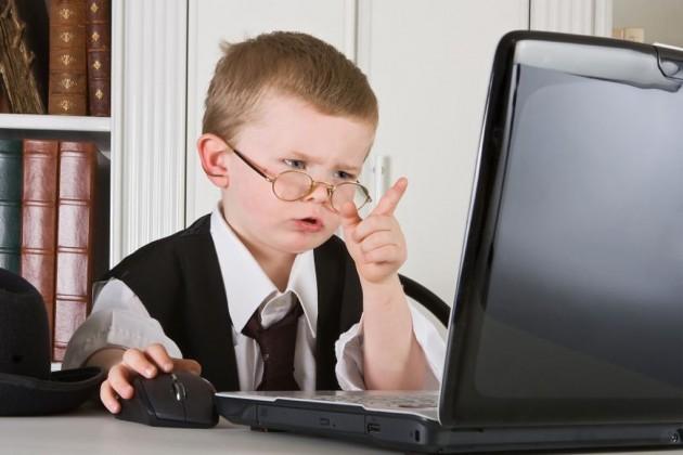 Серьезный ребенок за ноутбуком