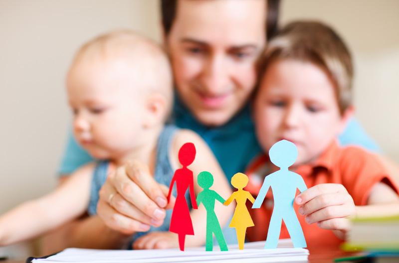 Мужчина и двое детей играются бумажными человечками