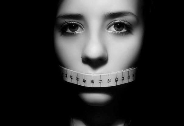 Девушка закрыла рот сантиметром