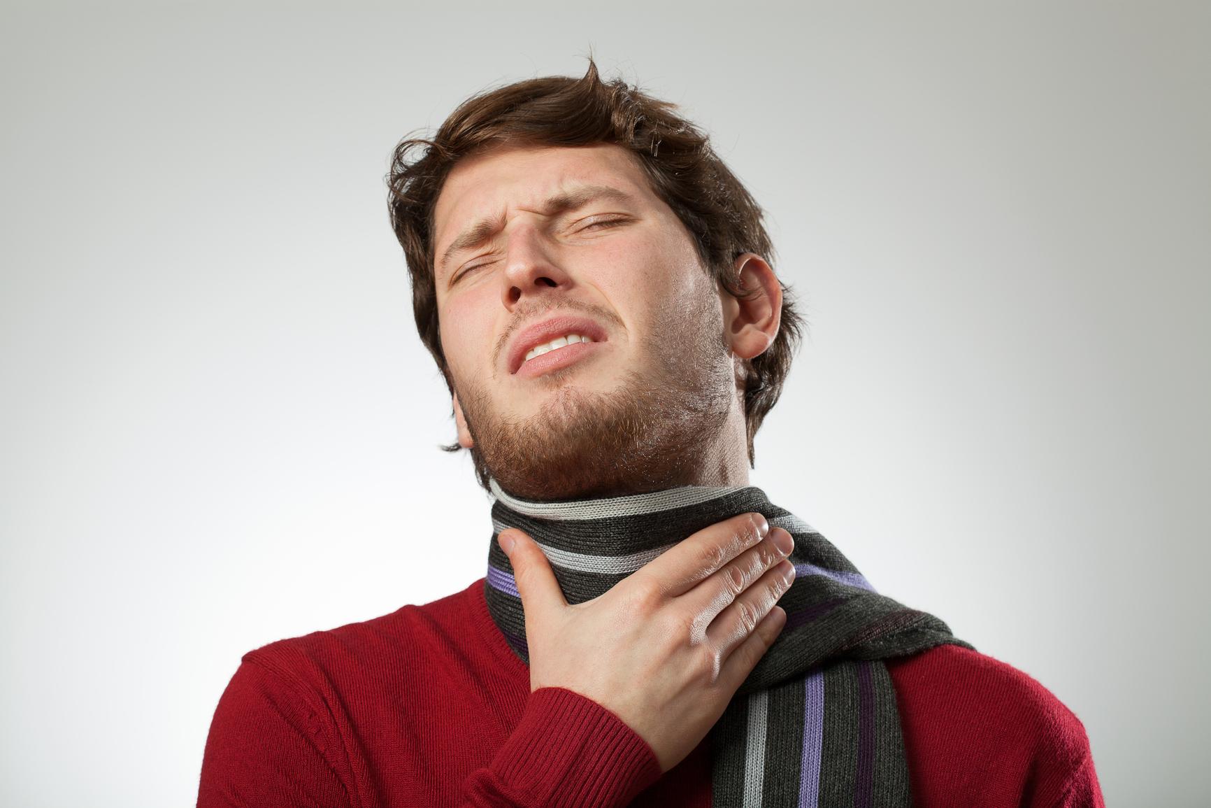 мужчина укутал горло шарфом