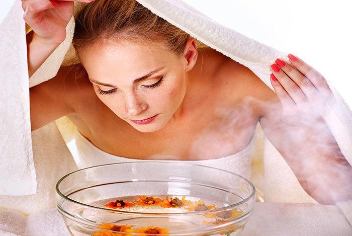 Девушка дышит паром над травяным раствором из пиалы накрывшись полотенцем