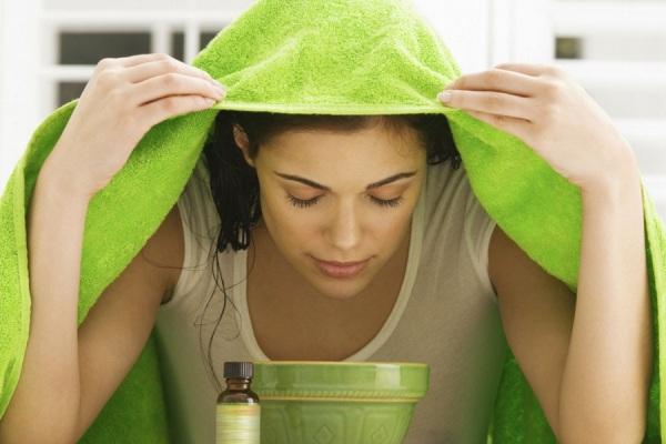 девушка накрылась полотенцем над чашей - делает масляную ингаляцию