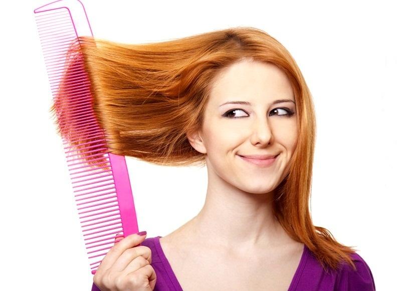 рыжая девушка улыбается косится на огромную расческу, которой расчесывает себе волосы
