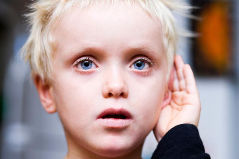 ребенок держит руку у уха