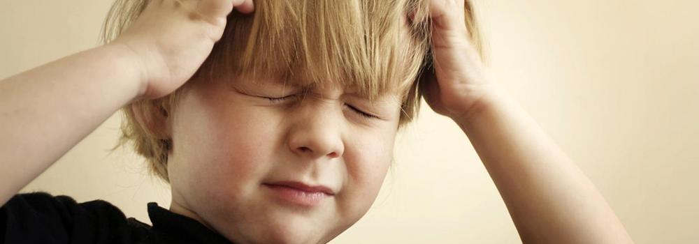 Закрыв глаза ребенок держится за голову