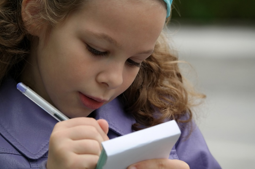 девочка пишет в блокноте